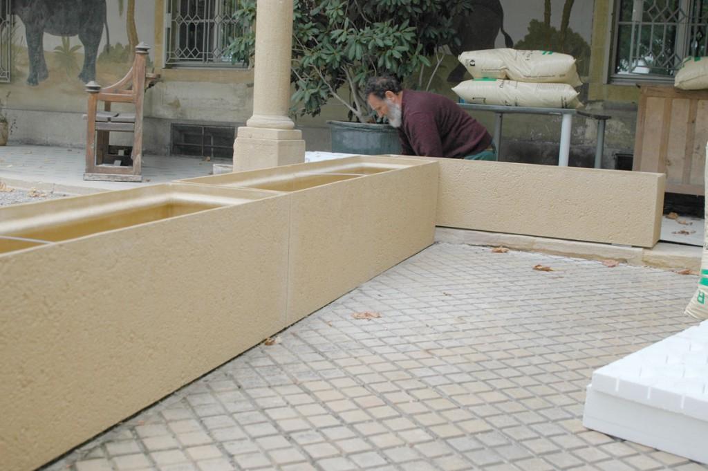 Création d'une terrasse avec des bacs de Müller Polyestère SA, façon pierre jaune assortis à l architecture du bâtiment.